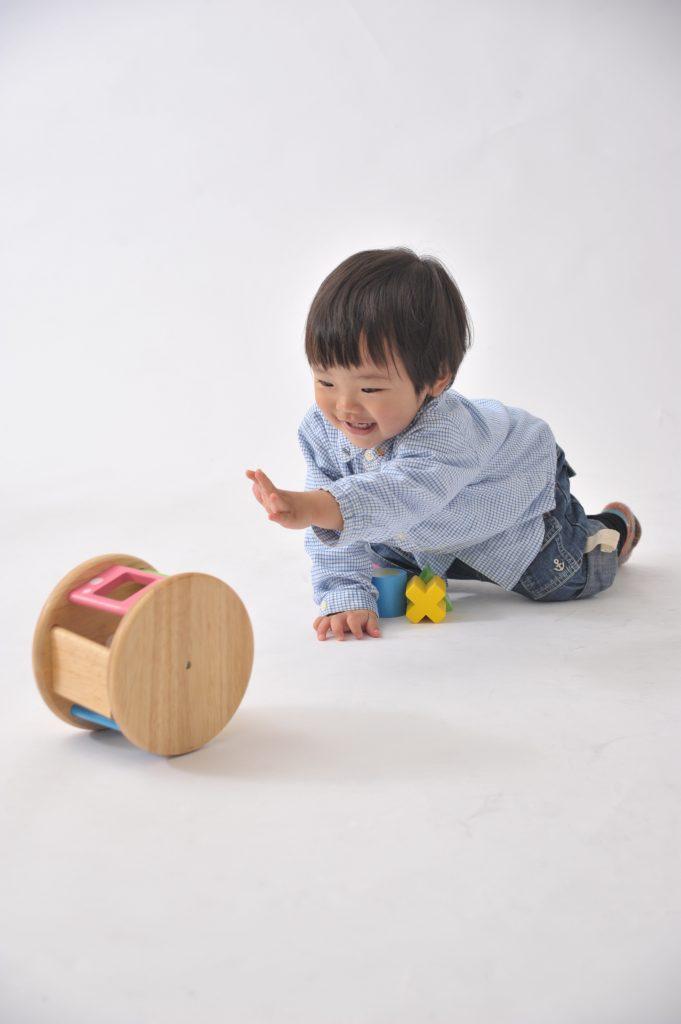 ハイハイをしておもちゃを追いかける赤ちゃん